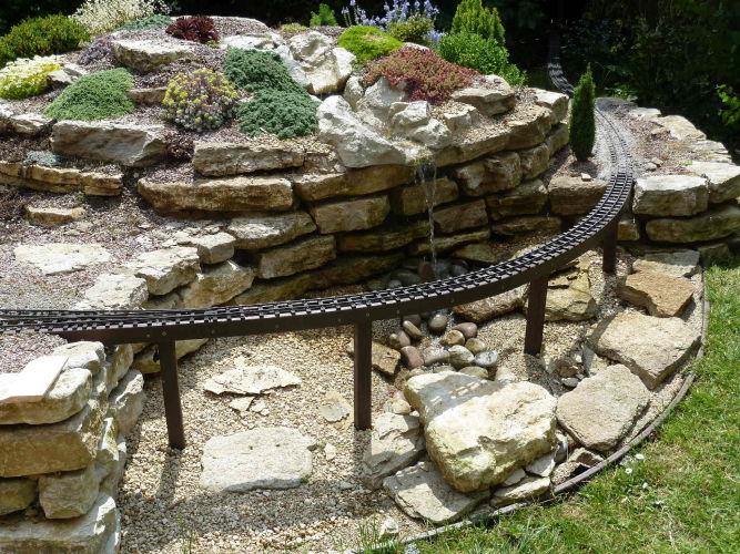 Recycled plastic ladder frame emerging from the alpine rock garden